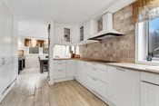 Delikate fliser over kjøkkenbenken som passer godt til rommet forøvrig.
