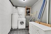 Fra badet er det praktisk inngang til vaskerom som ahr flislagt gulv, og delvis flilagte vegger.