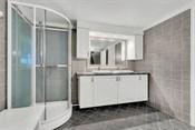 Dusjkabinett, en hvit og romslig baderomsinnredning samt tilhørende speil.