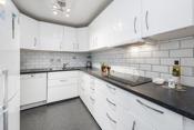 Kjøkkenet har en lys innredning og hvite fliser over laminat benkeplater.