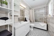 Badet er flislagt med varmekabler og har badekar med dusjforheng og plexiplate på vegg.