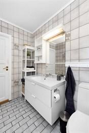 Badet i 1. etasje er eldre, men er oppgradert med en ny, hvit baderomsinnredning.