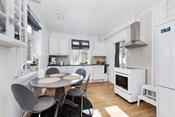 Kjøkkenet er innredet med hvite profilerte eikefronter og laminert benkeplate med nedfelt dobbel oppvaskkum.