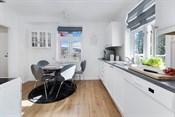 Fra den mindre stuen, tar en seg inn i et enkelt kjøkken.