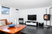 Lys og koselig kjellerstue med peiovn, vindu samt fliser og varmekabel i gulvet