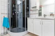 Badet har fliser på gulv og vegg- installert dusjkabinett og wc, lys innredning