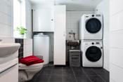 Stort bad med veggtoalett, dusj på gulv/vegger med glassdører, innredning med servant, samt opplegg for vaskemaskin.