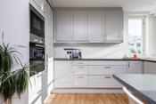 Kjøkken med integrert komfyr, stor induction platetopp, oppvaskmaskin, kjøl og frys, ventilator og micro.