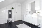 Bad med veggtoalett, dusj på gulv/vegger med glassdører og innredning med servant.