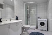 Bad med toalett, dusjkabinett, innredning med servant og opplegg til vaskemaskin