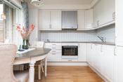 Lyst og delikat kjøkken med integrerte hvitevarer