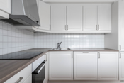 Kjøkken med integrert komfyr, platetopp, oppvaskmaskin, ventilator kjøl og frys.