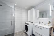 Badet er innredet med dusjhjørne med foldedører, servant med underskuffer, vegghengt toalett og speil med lys.