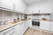 Aubo kjøkkeninnredning med hvite glatte fronter og laminerte benkeplater.