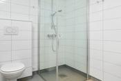 Pent bad med vegghengt wc og duskabinett med glassdører