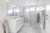 Flislagt bad i underetasjen med nøytrale fliser på gulv og vegger. Det er elektriske varmekabler i gulvet