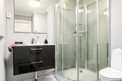 Gulv med fliser og vegger med malt baderomspanel. Servant på skap med grå front. Gulvstående wc. Dusjkabinett. El-vifte i vegg. Varmekabler.