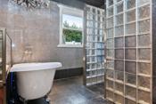 Badet har fliser på gulv og vegg med varmekabel- badekar og dusjsone