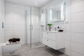 Delikat flislagt bad med vegghengt toalett, dusjhjørne og opplegg for vaskemaskin