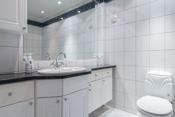 Bad i 1. etg. tilknyttet hovedsoverom med flislagt gulv og vegger.