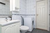 Bad med dusjkabinett, toalett, innredning med servant og opplegg for vaskemaskin