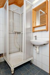 Badet er flislagt med dusjkabinett og wc