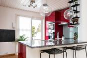 Kjøkken med integrerte hvitevarer og utgang til terrasse