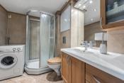 Bad med vegghengt toalett, dusjkabinett, opplegg for vaskemaskin, servant med skapinnredning.