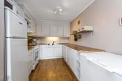 Kjøkkeninnredning med lyse profilerte/glatte fronter, benkeplater i heltre, rustfri benkebeslag med oppvaskkum, ventilator og opplegg for oppvaskmaskin.
