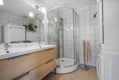Bad med dusjkabinett, dobbel servant med skuffer og plass for vaskmaskin.
