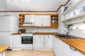 Kjøkkeninnredning med lyse glatte/profilerte fronter og heltre benkeplate.