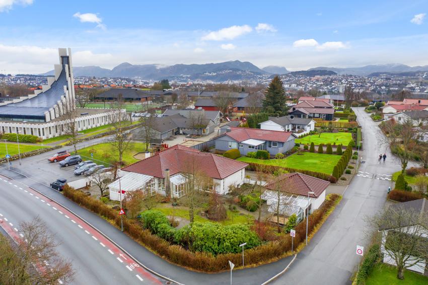 Enebolig med stor grunnflate, garasje på 37 kvm, uthus på 23 kvm, hagestue på 23 kvm og takoverbygd terrasse.